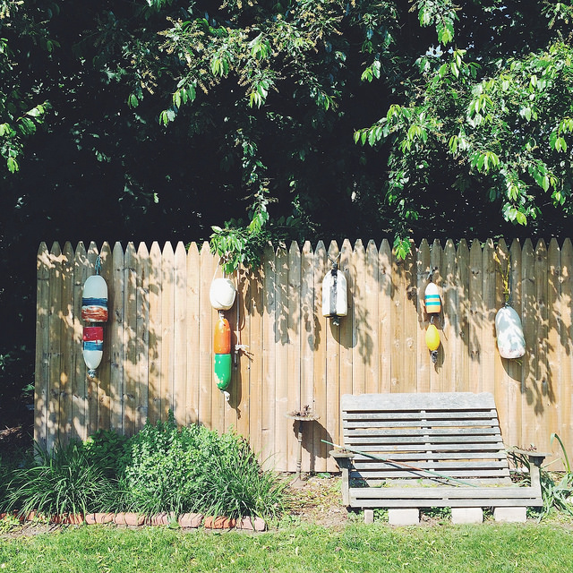 Painted buoys line a picket fence.