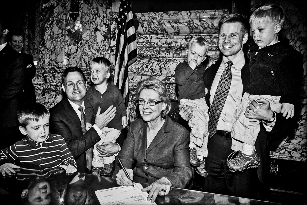 Washington state Governor Christine Gregoire signs marriage equality legislation in Olympia, Wash., on February 13th, 2012. Gregoire is flanked by state representative Jamie Pederson and his partner Eric Cochran Pedersen and their three boys.