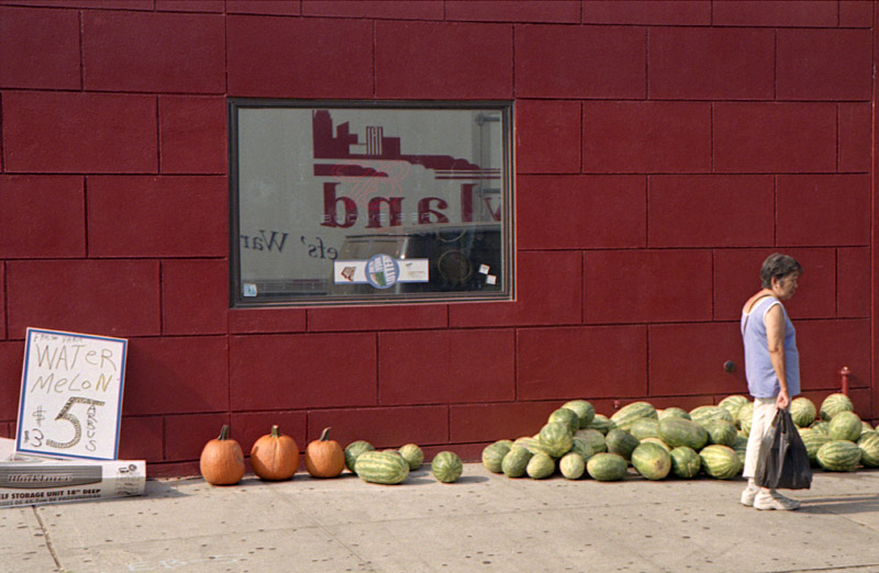 A woman loiters near a makeshift watermelon stand. Greenpoint, Brooklyn 2008
