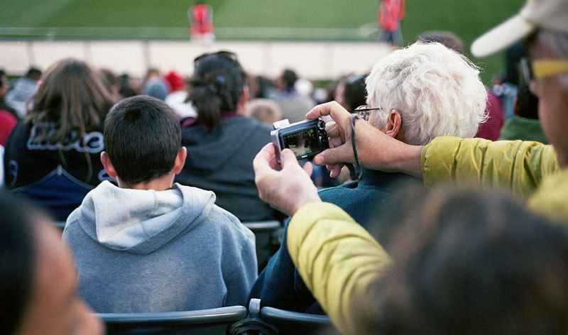 Man taking a picture of his grandson at the soccer game.     Commerce City, CO 2013