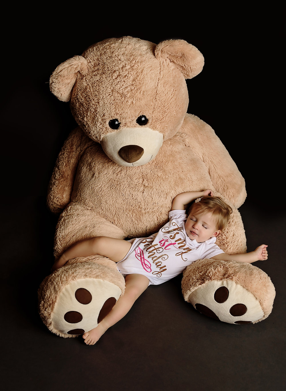 Baby girl asleep with giant stuffed bear