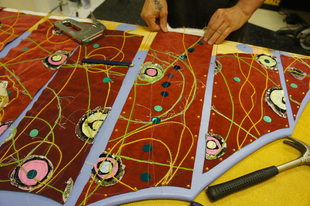 Decorated fabric being tacked down to the spinosaurus' plywood neural spine.