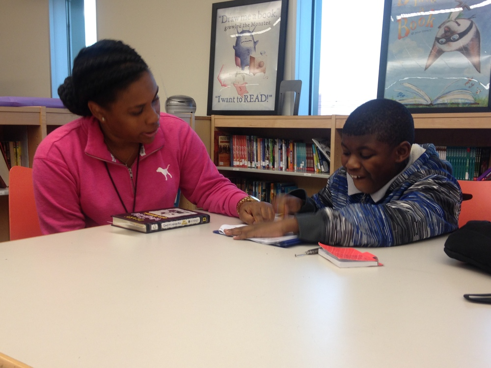 Volunteer Adrene works with 3rd grader Dismas on his homework during aftercare.