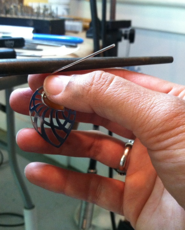 I use a mandrel as a form to wrap the wire around. This results in a nice smooth bend.