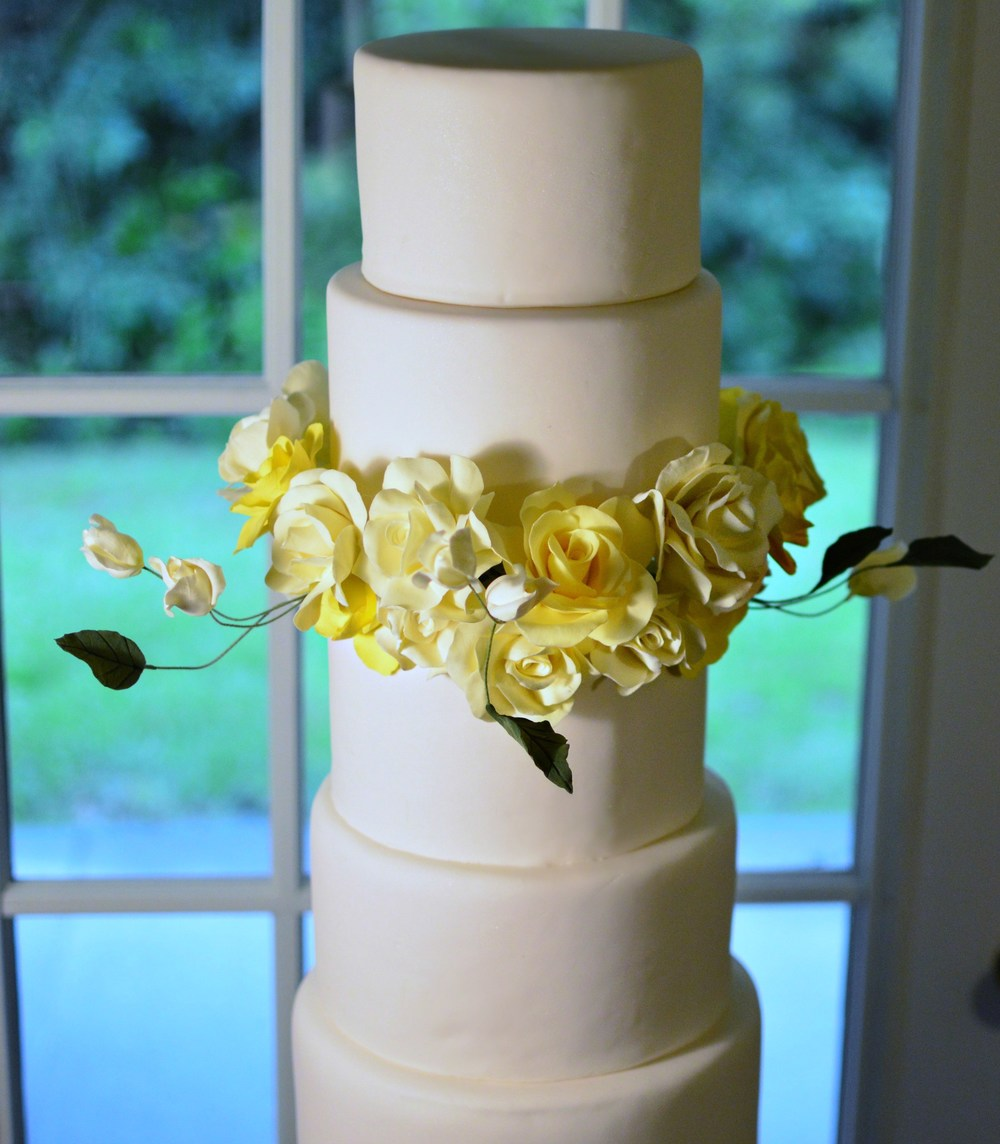 The Cake:  We choose to create an array of lightness to make our  6 tier Wedding Cake.  This soft ombre flourish looks amazing together,  We mixed some of the softest & whitest of yellow color.   We also created a soft butter and bright canary yellow to complete the look.  For more information on Petal Smitten email us at Larita334@gmail.com