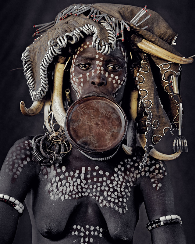 """Mursi women are known all over the world for wearing clay plates in their lower lips… It is said that the lip plates were invented to make Mursi women less attractive to slave traders. In the tribe today, the bigger the lip plate, the more cattle the girl is worth by the time she is traded into marriage."""