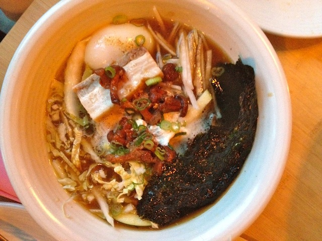 The Tanakasan Ramen made with rich pork & sweet corn broth, pork belly, soft egg, black garlic butter, scallion, shiitake, and wavy noodles.