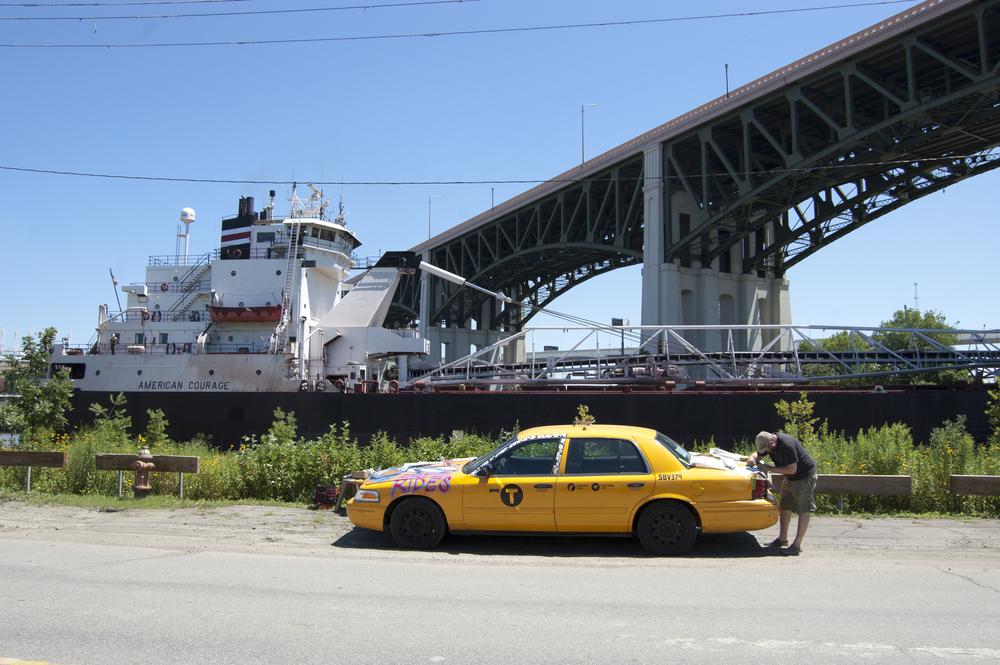 Geologic Cognition Society explores accretion & erosion for Conatus Taxi - Dru McKeown installing the analog sensors (July 2015). American Courage floats by in the background near Ohio City.