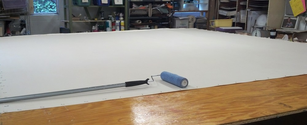 Shrinking and sizing the canvas prior to painting.