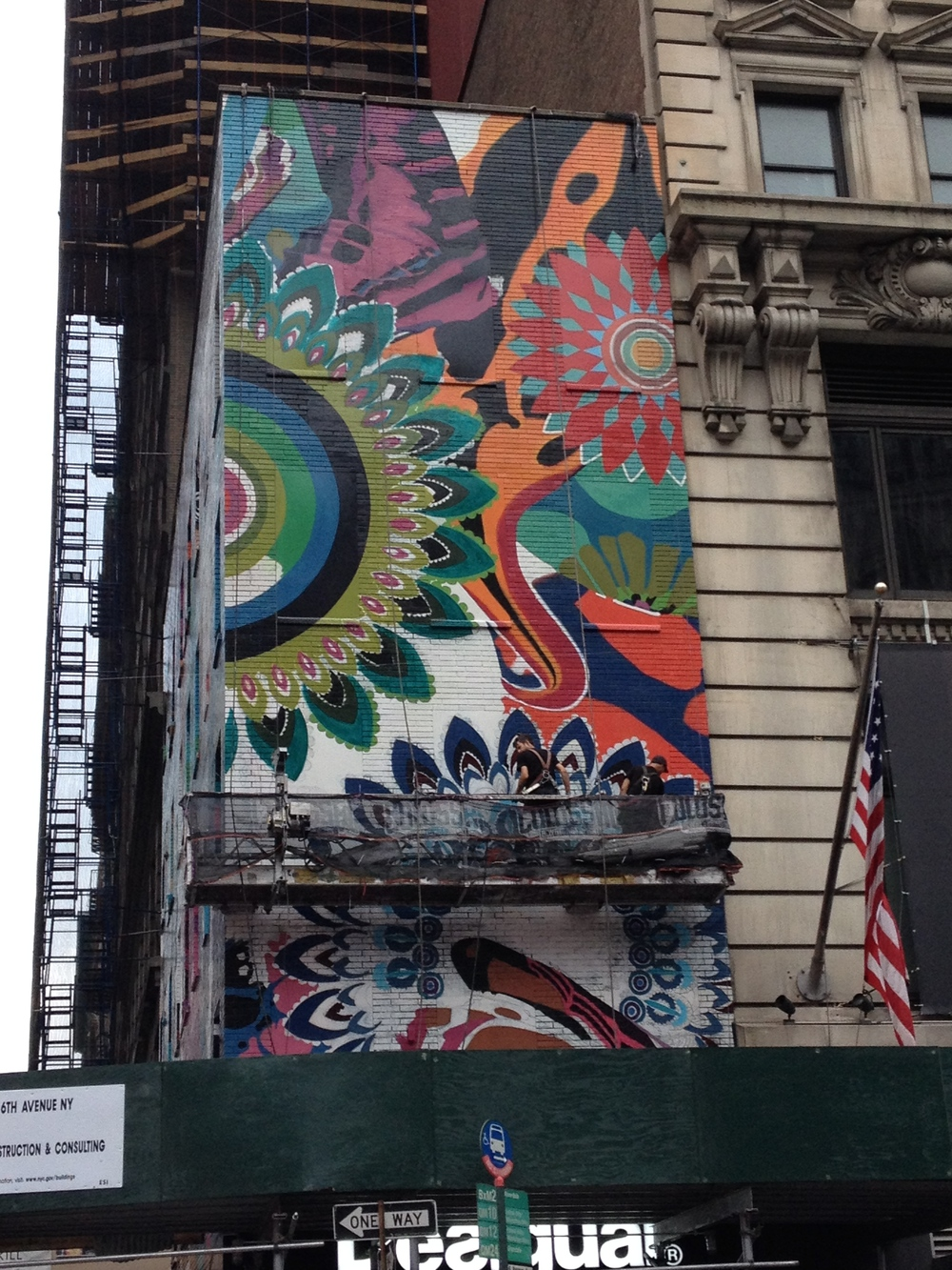 Desigual painting on a corner in Manhattan. Notice the 2 guys on the scaffolding. The art is huge!