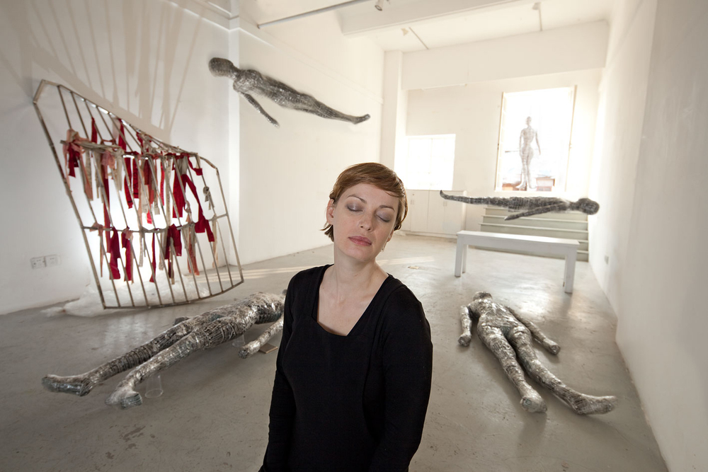 Susanne Junker photographed by  Eric Leleu  at stage候台BACK 696 with floating  self dolls , shortly before the eviction of artists, 2011