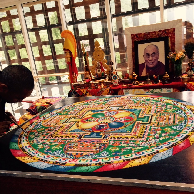 Tibetan monks put the finishing touch on a sand mandala at the Aspen Art Museum.