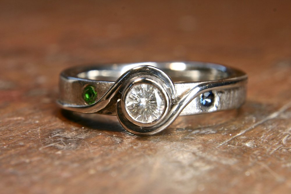 Bespoke palladium ring, set with a large moissanite, fair trade sapphire and a lab grown emerald.