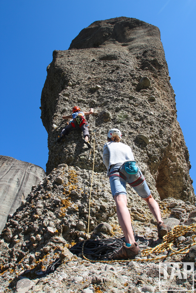 Pictured is Read climbing up the first pitch of the Gordian Knot; a forty metre high thumb of twisting conglomerate stone, ten metres at it's widest point, set at the forested intersection of four much higher monoliths. At first glance it appears as if you could push the tower right over, the base is so skinny. The conglomerate hide of the towers is a unique feature in the climbing world. Pebbles as small as you can imagine and stones the size of your head seem to be temporarily glued in to the soft sandstone bedrock, with up to 70% of their bulk hanging in the air.