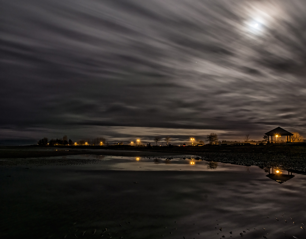 Moving clouds reflect in the moonlight at parksville Beach