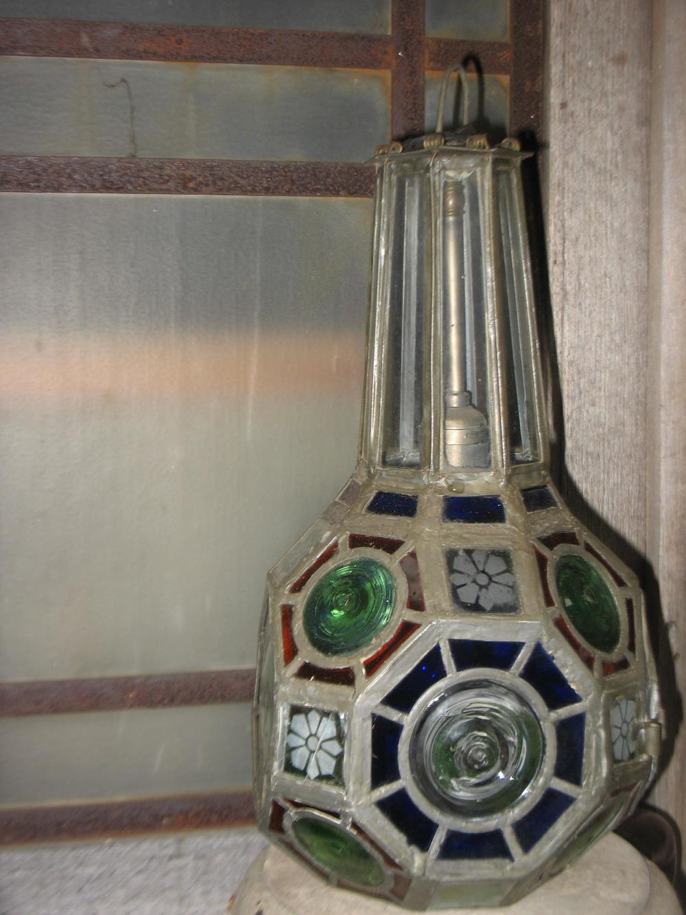 This is a magnificent stained/art glass light fixture.  Octagon shaped it is difficult to give you exact measurements, but it is 16 inches tall and can be any length with a chain placed as you need it to be for your ceiling. There is everything in this fixture, green bulls eyes, etched flowers, blue pieces of small glass around large bulls eye and red small pieces of glass around small bulls eyes.    This piece was stolen if anyone recognizes it, please contact us