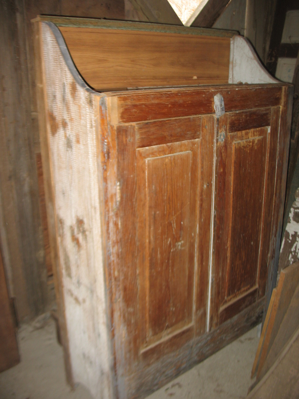 Primitive cupboard with original paint at ends.  Two doors open to reveal 4 shelves which are 38 inches long and 13 inches wide. The cupboard measures 5 feet tall from top to bottom in the back.  Is 44 inches wide and 15 inches deep. It is 51 inches tall in the front which means that the back piece is 9 inches. Price: NA