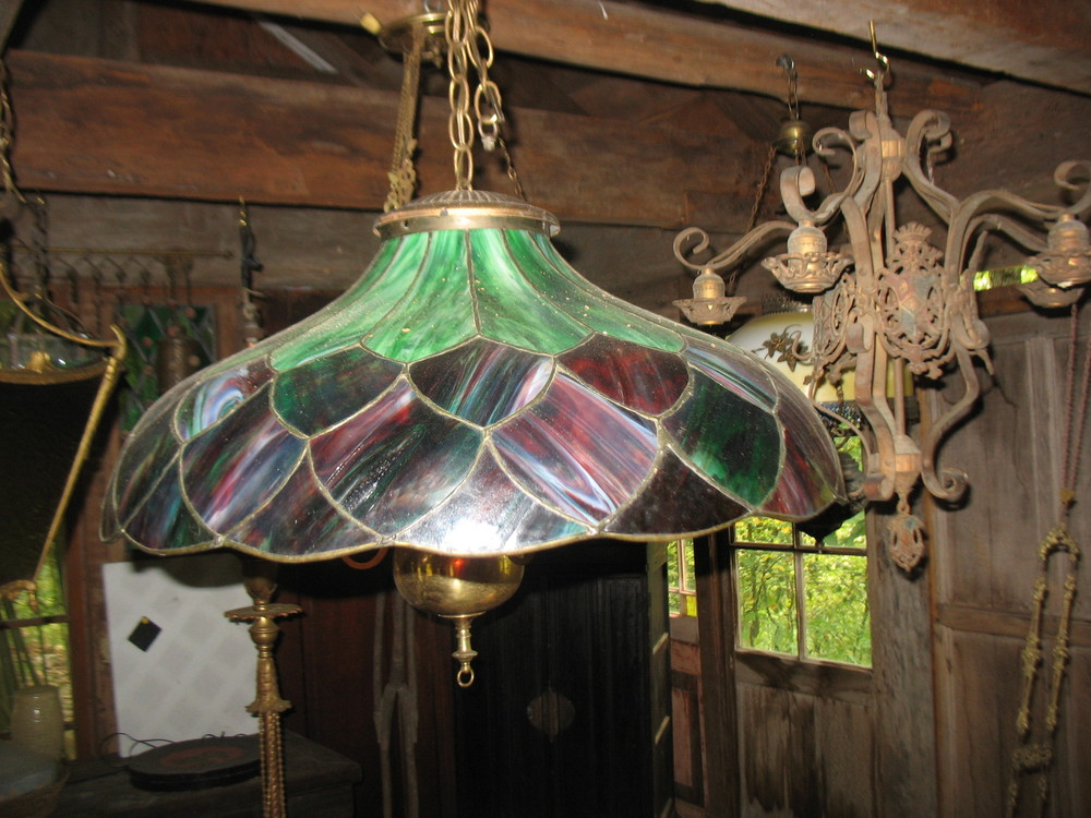 This is a brass chandelier of green and multi-colored glass with brass chains. Wonderful over your dining room table or table in family room.   SOLD
