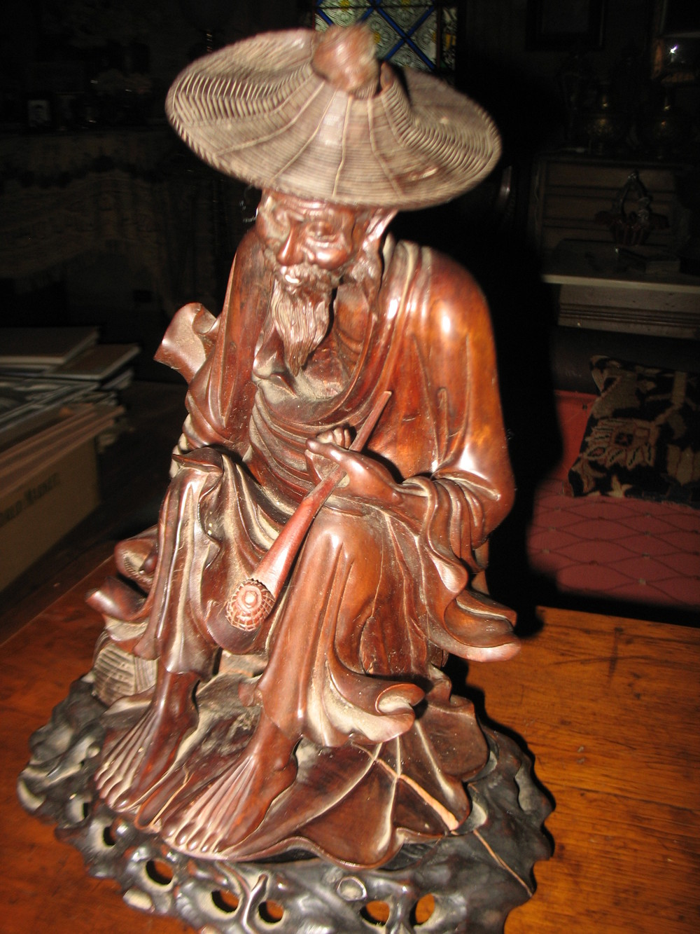 Chinese Rosewood Carving of old man with basket on one side holding a pipe. All intricately carved and is seated on carved base.  12 inches tall and base is 28 inches around.   Price upon request