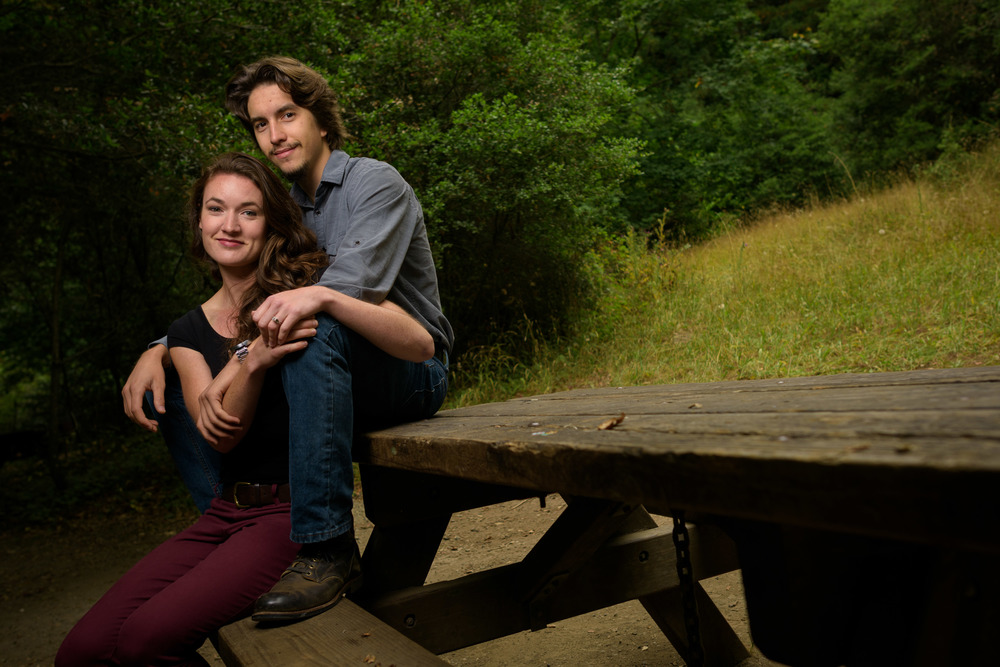 Couple sitting on a bench in the redwood forest - Engagement Photos in Nisene Marks Forest in Aptos, CA - by Bay Area wedding photographer Chris Schmauch