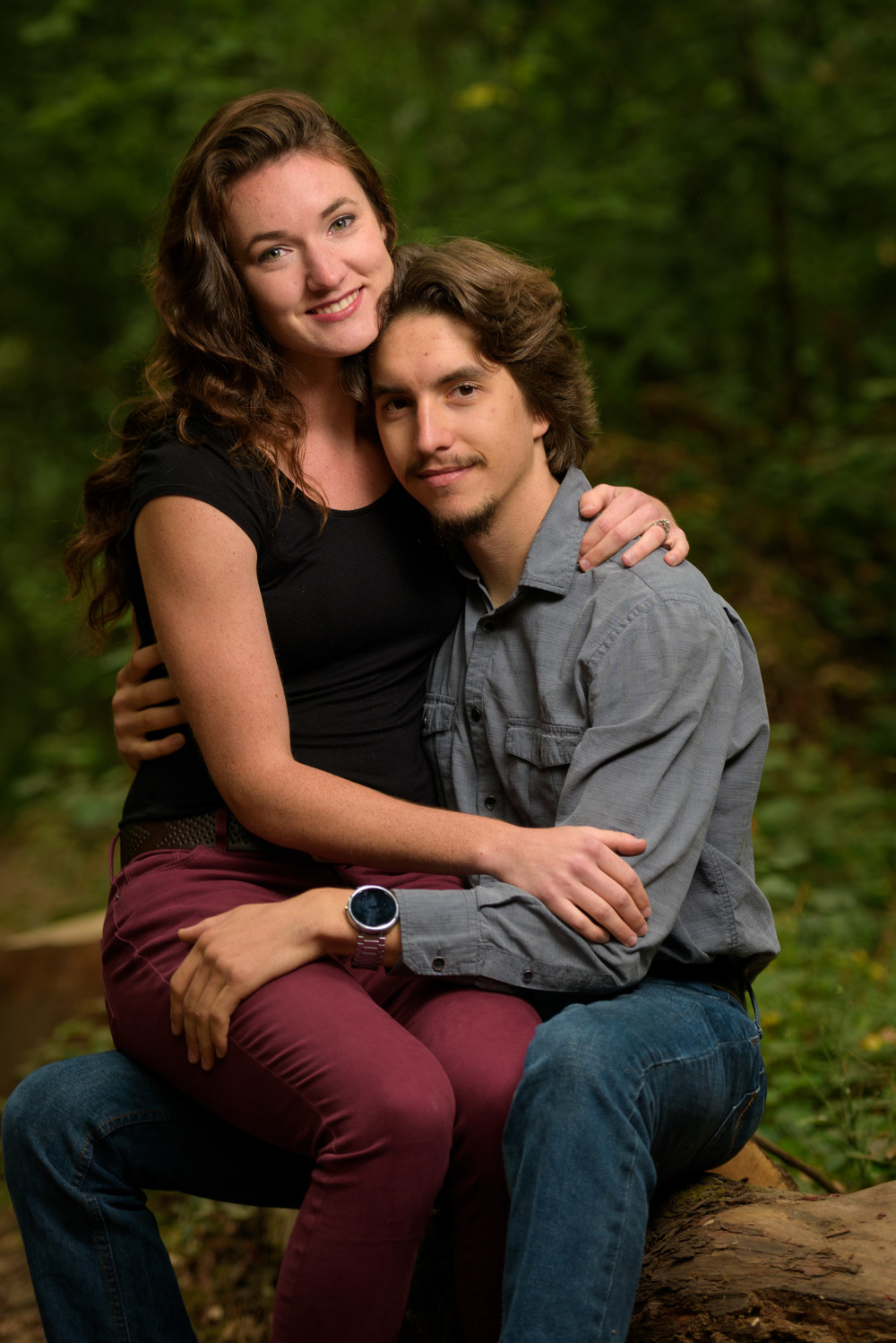 Couple looking at camera while sitting on a log in the forest - Engagement Photos in Nisene Marks Forest in Aptos, CA - by Bay Area wedding photographer Chris Schmauch