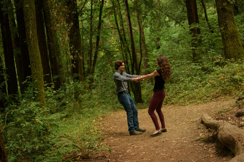 Couple swinging around in circles in the forest - Engagement Photos in Nisene Marks Forest in Aptos, CA - by Bay Area wedding photographer Chris Schmauch