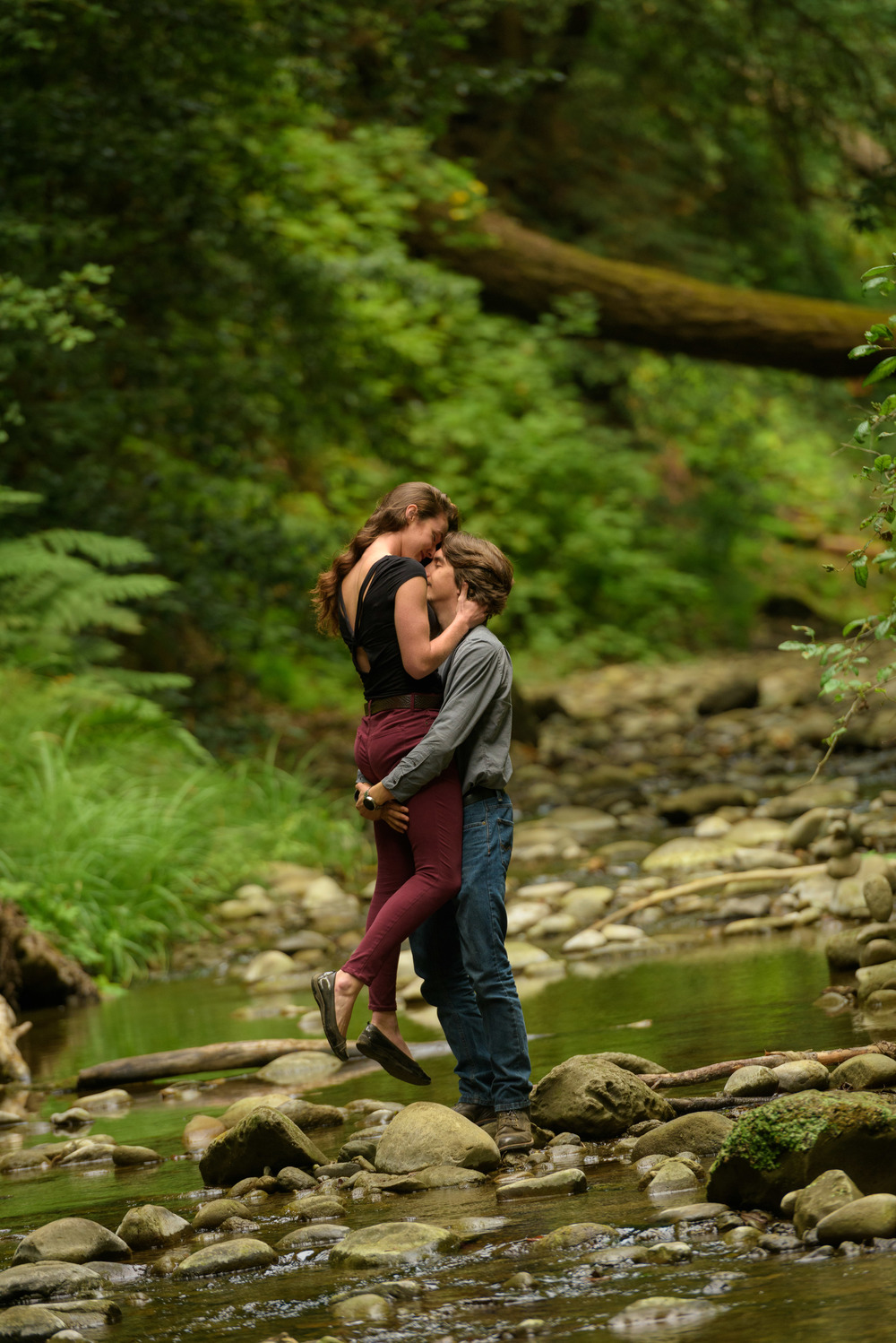 Man lifting up his fiancee for an intimate moment in the creek - Engagement Photos in Nisene Marks Forest in Aptos, CA - by Bay Area wedding photographer Chris Schmauch