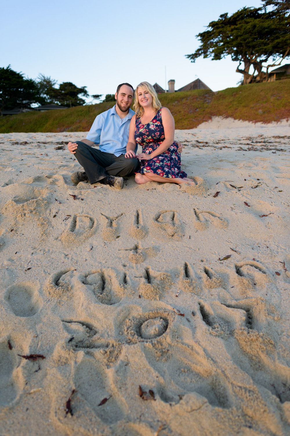 couple sitting on sand with wedding date written in sand - Stewart's Cove - Carmel Engagement Photography - photos by Bay Area wedding photographer Chris Schmauch