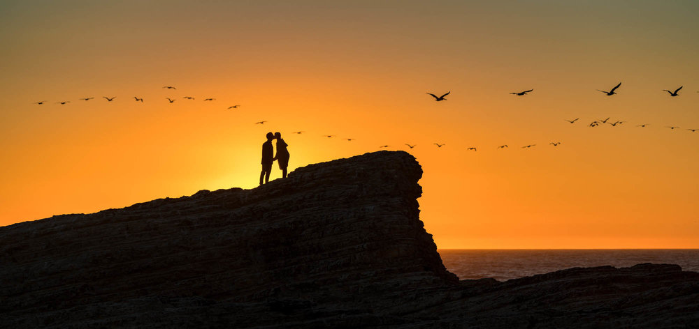 Romantic sunset engagement at Panther Beach - with pelicans flying in formation - photo by Bay Area wedding photographer Chris Schmauch www.bayareawedding.photography