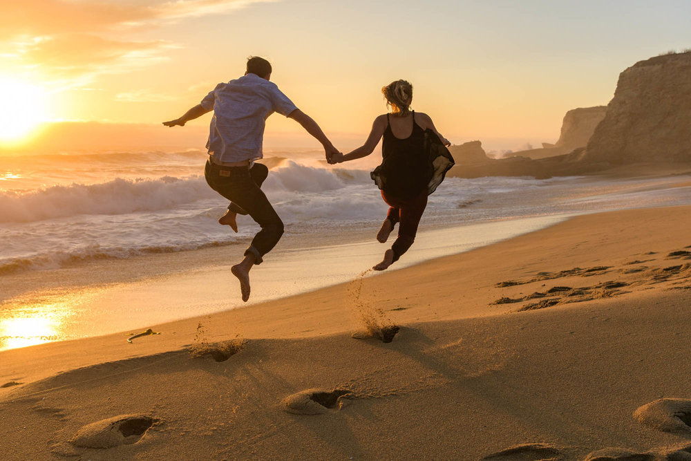 Couple jumping off a sand dune with the ocean in the background – Panther Beach, Santa Cruz Couples Portraits – by Bay Area wedding photographer Chris Schmauch
