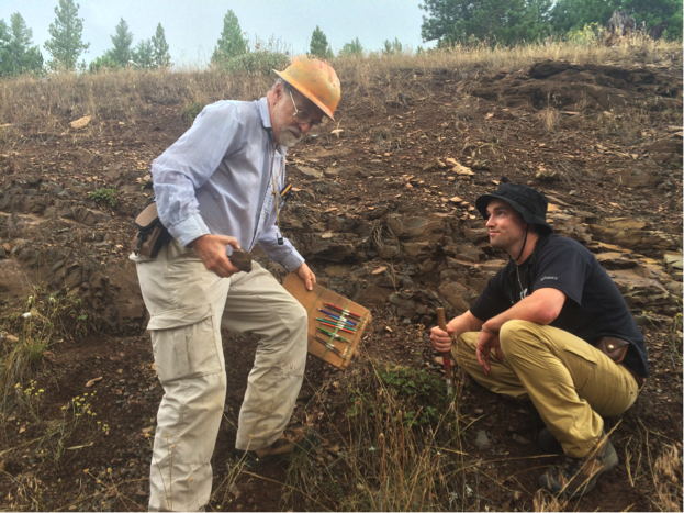 SPENCER JONES  AND JAD D'LLURA TAKE A HAND SAMPLE FROM AN OUTCROP.