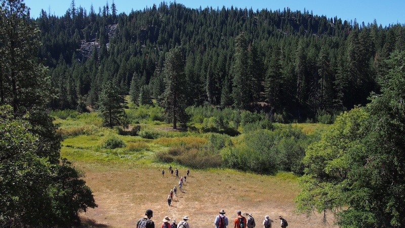 The group follows Michael Parker down into Fredenburg Meadow to search for a beaver dam. see the 3-MILLION YEAR OLD LAVA FLOW at the upper left. K Boehnlein photo