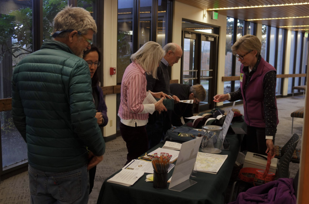 Community members interact at the registration table.