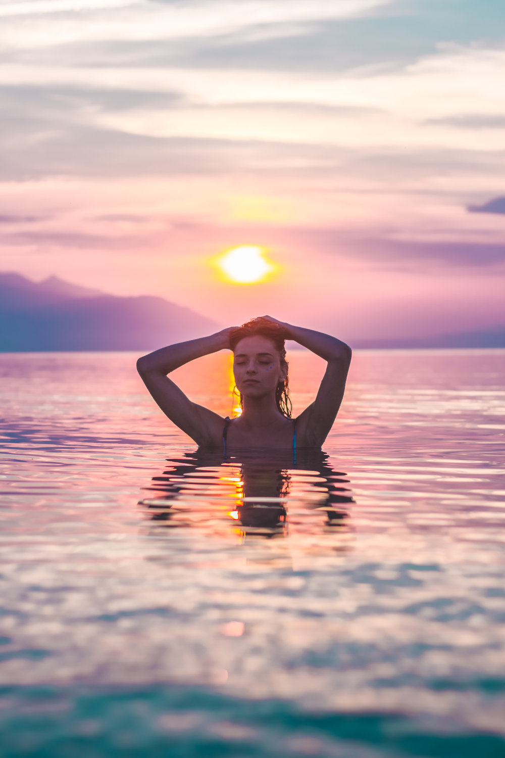 Meditation is swimming in the ocean at sunset surrounded by mountains.