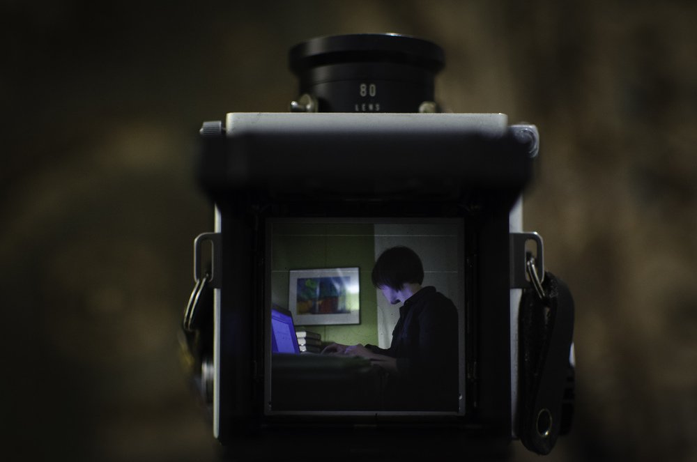 Standing above, looking through the viewfinder.