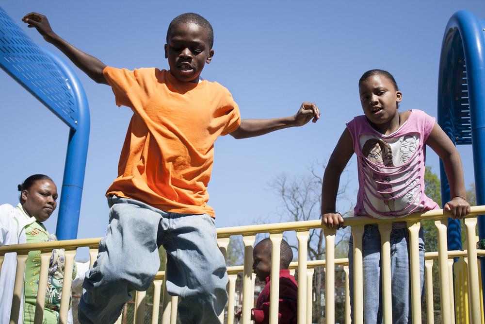 Rayquan, Rasheeda's oldest son, jumping off the play set.