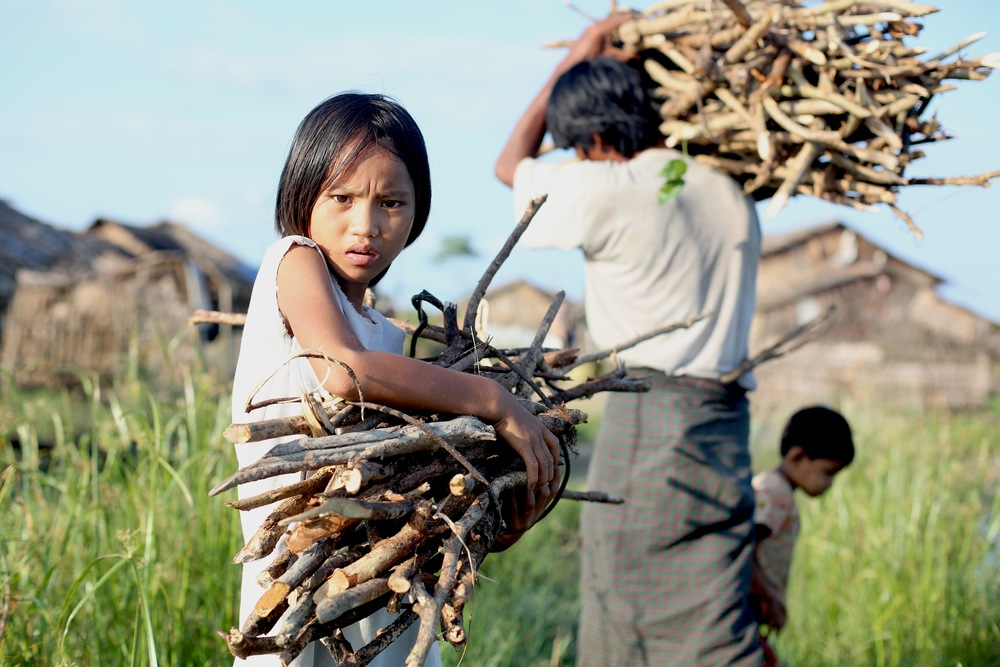 A girl in Myanmar collects wood with her family
