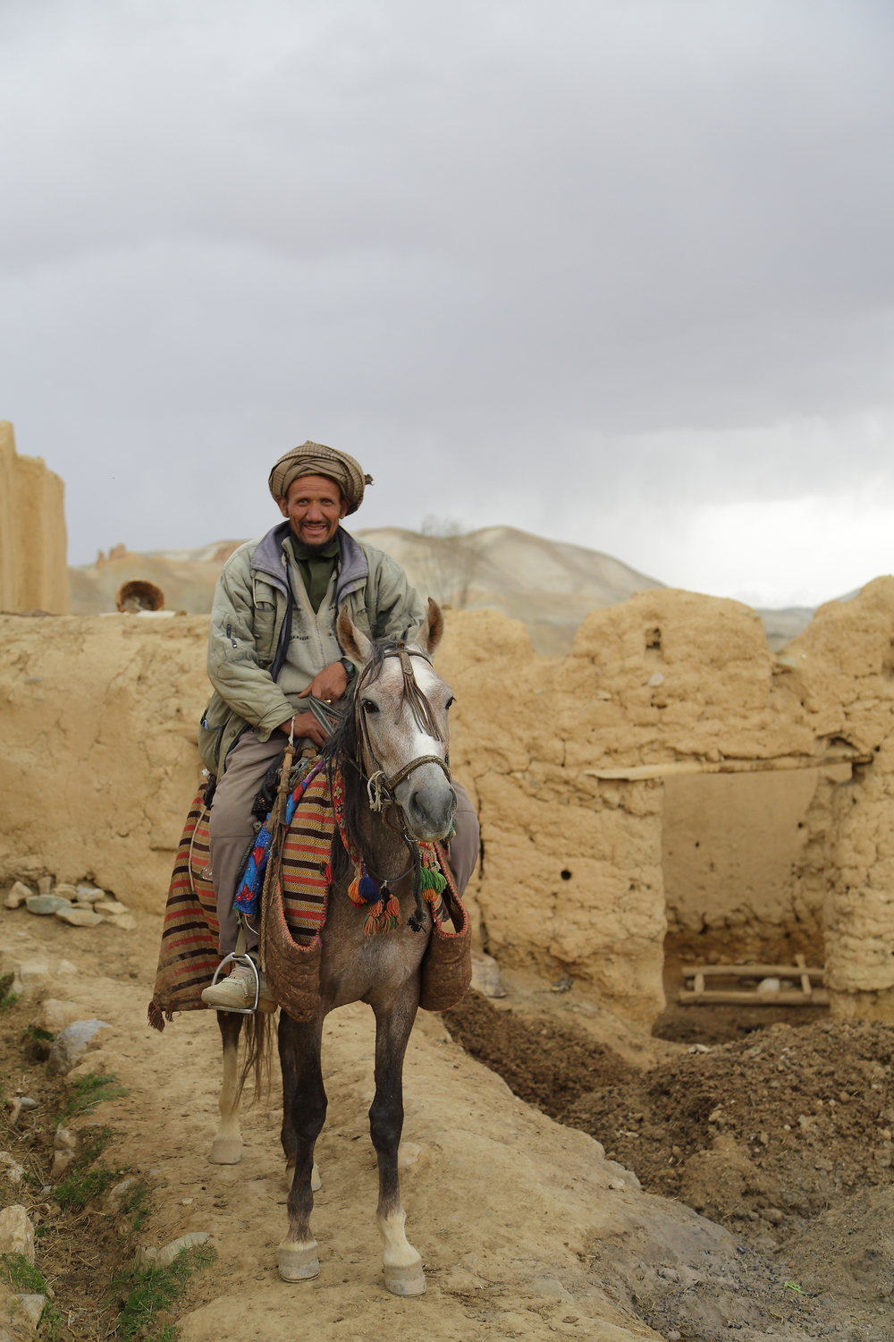 An Afghan man rides his horse through his village