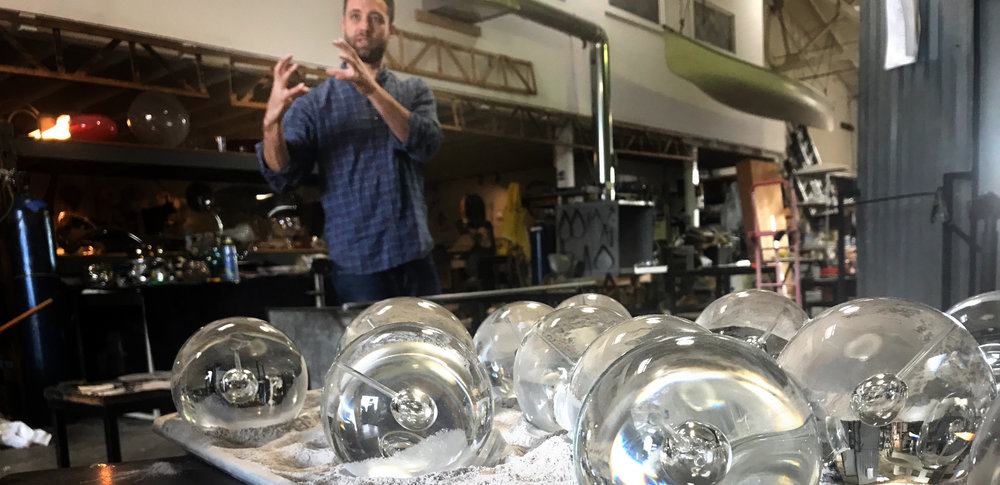 Glass artist Zak Timan explaining the process of forming the award spheres