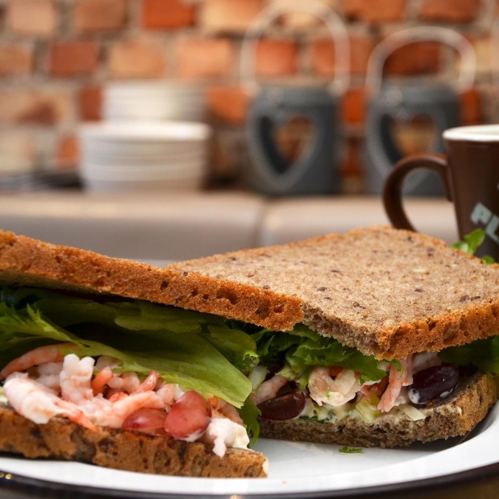 REKESANDWICH    Lenas brød, håndpillede reker, purre, salat, druer, aioli (majones, rømme, hvitløk, salt, pepper, sitron).     95,- (ta med 87,-)     1/2 sandwich 65,- (ta med 59,-)