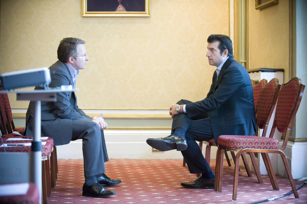 Candid Conference Portrait of two businessmen in suits sitting talking
