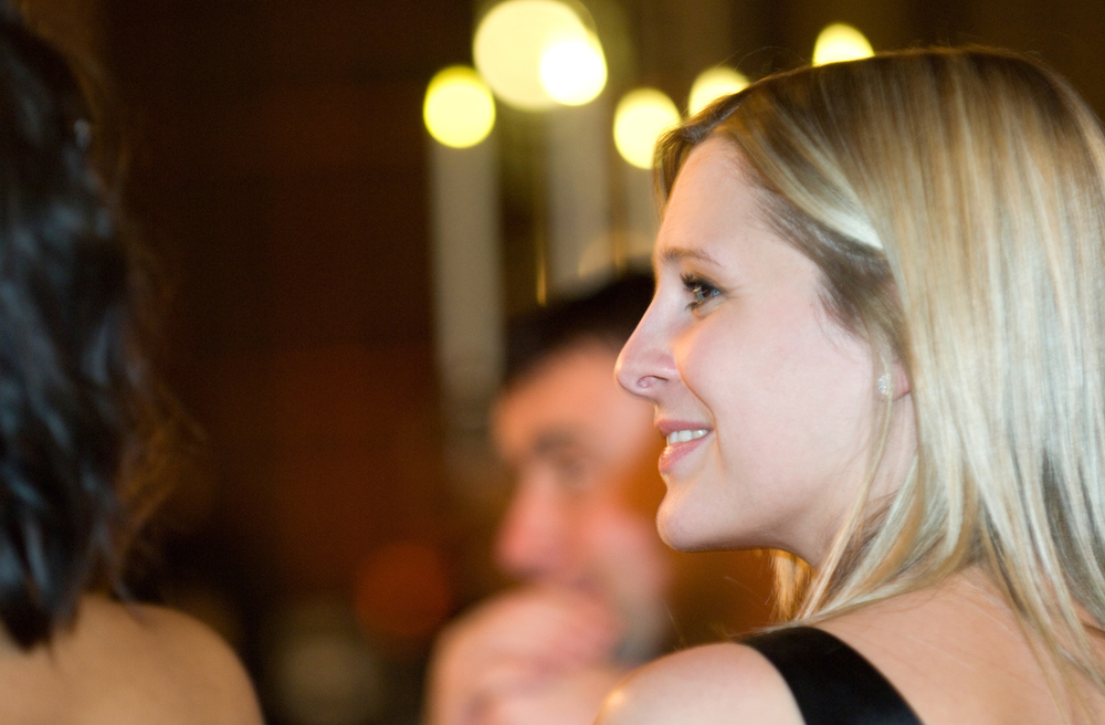 Candid portrait of a woman smiling at a black tie evening event
