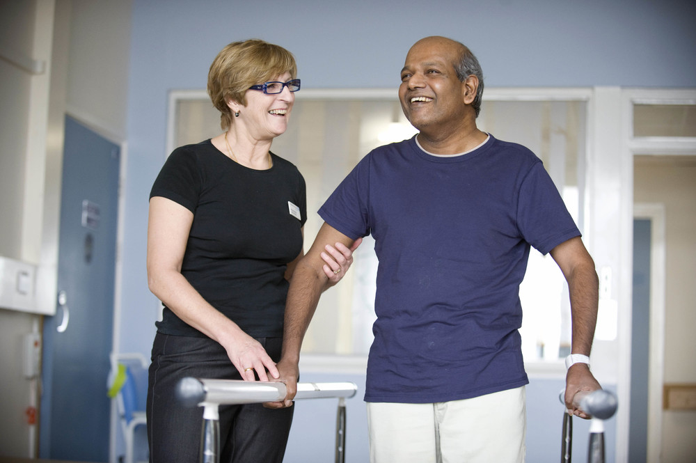 A medical professional helping a patient to walk using bars in rehabilitation