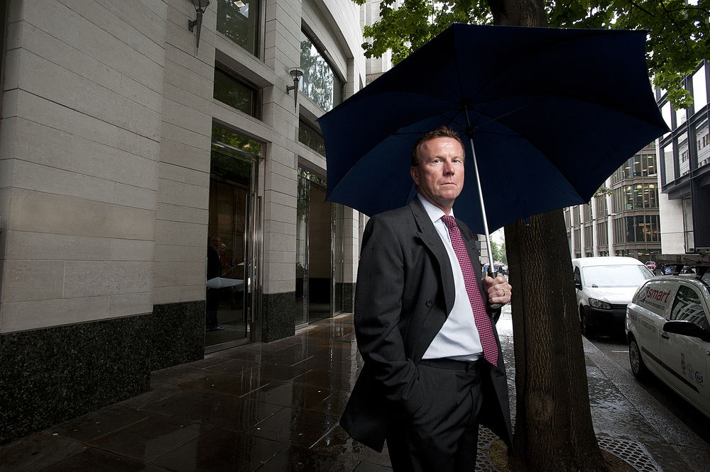 Corporate portrait of a businessman in a suit with an umbrella