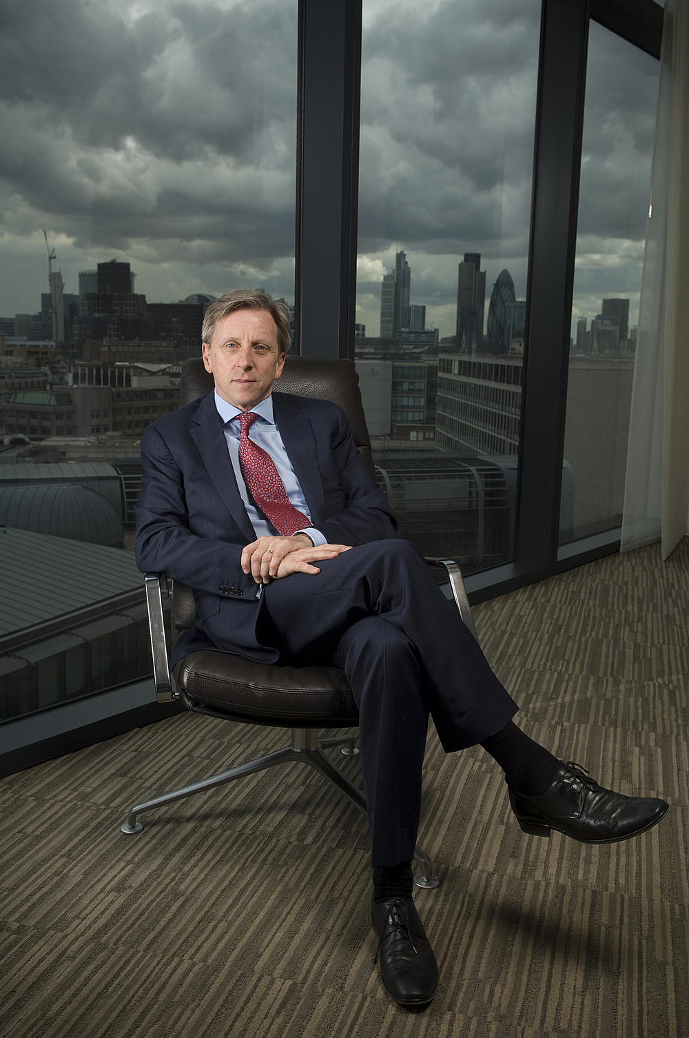 Corporate portrait of a business man in a suit sitting cross legged in front of a london skyline