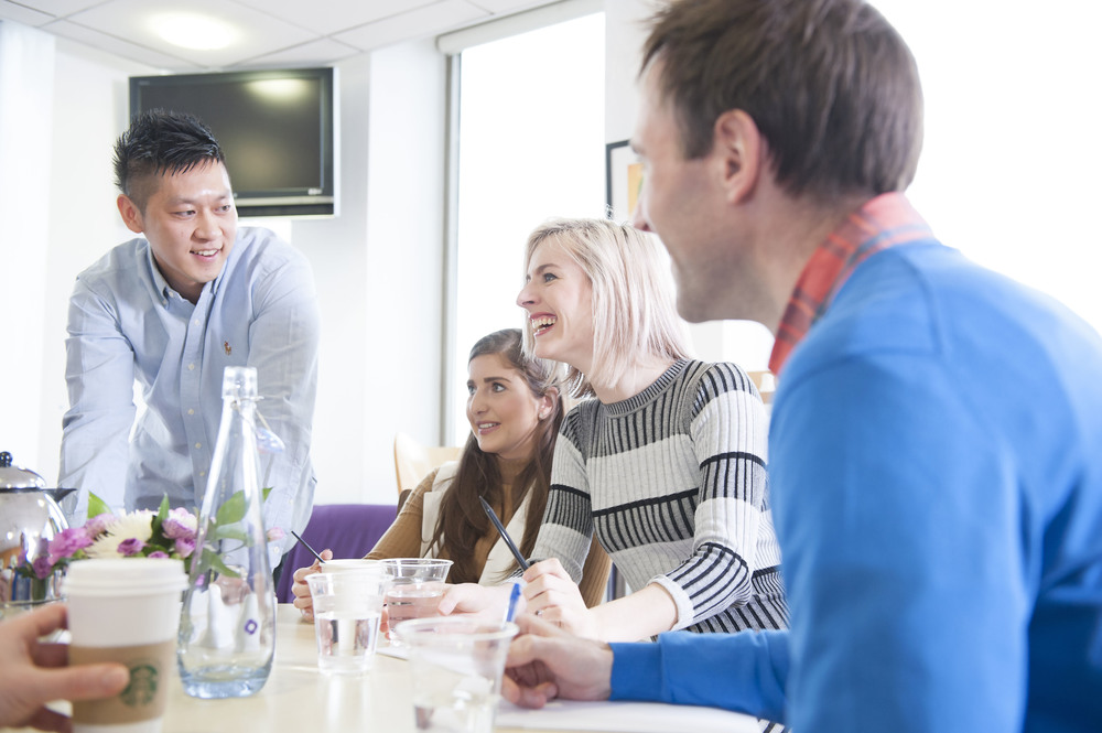 People having and informal meeting in an office canteen Laughing