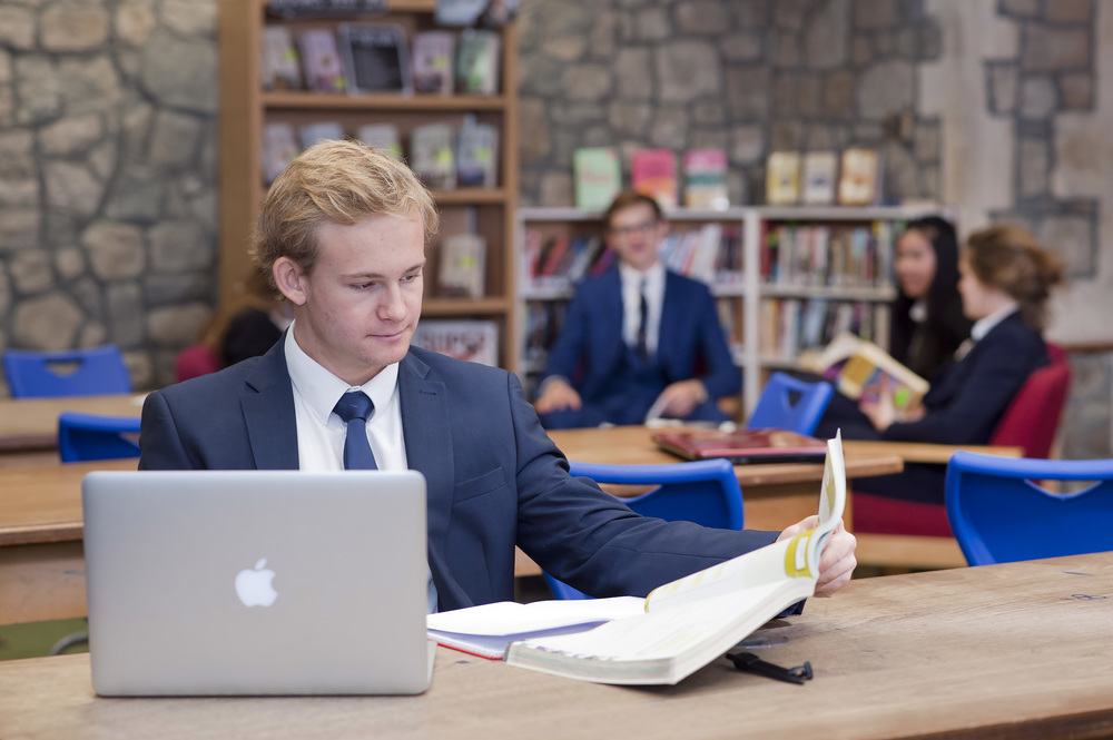 Marketing portrait of a student studying in a library with a MAC