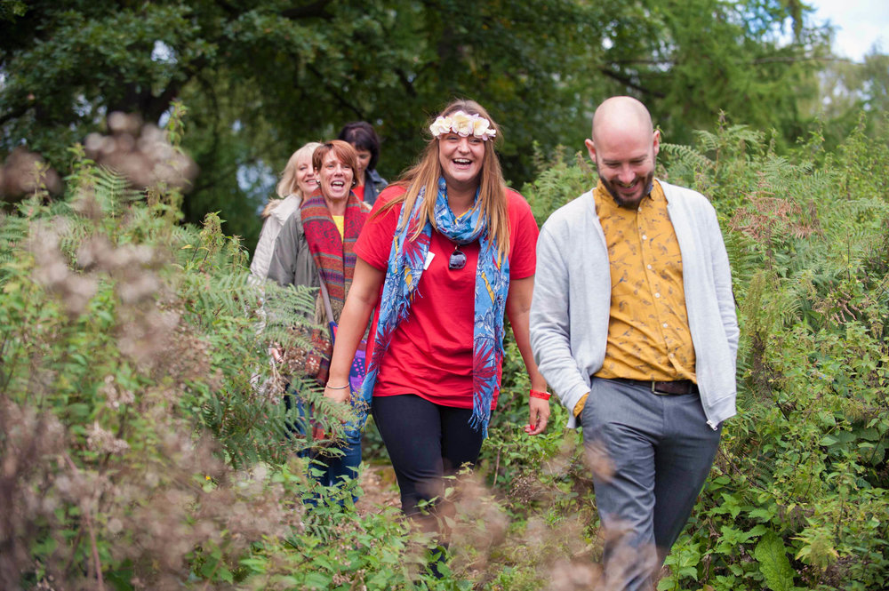 Candid style image of people walking in woodland laughing