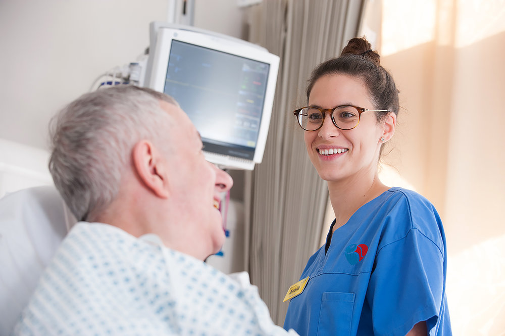 Portrait of Nurse smiling looking at a patient in a hospital bed