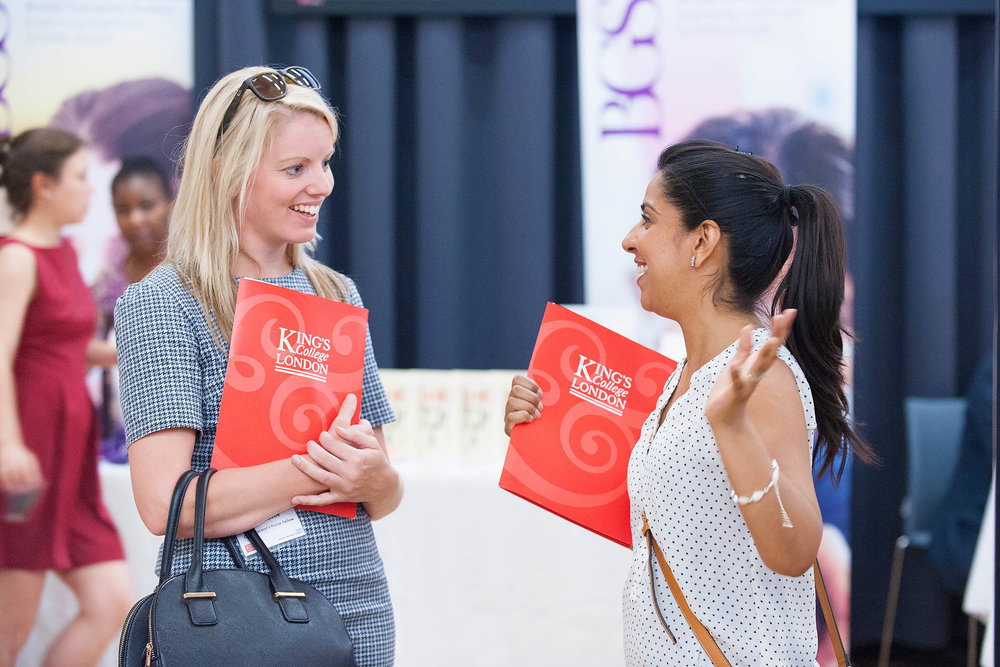 Candid portrait of two women attendees talking and laughing at an event at Kings College London